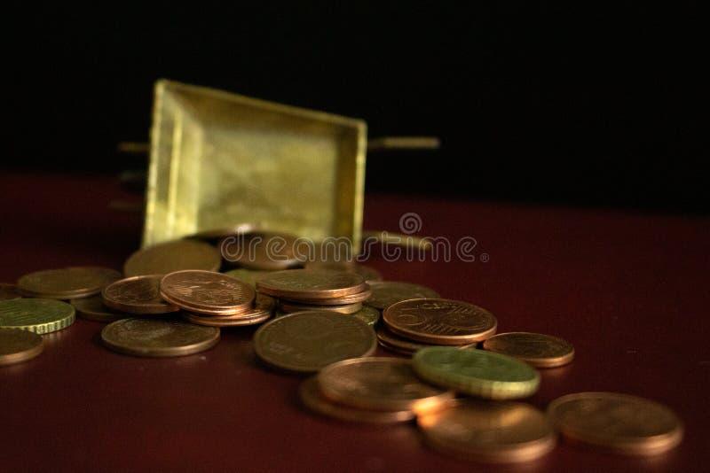 Uma série de moedas que caem de um carrinho de mão dourado do vintage no fundo escuro imagens de stock