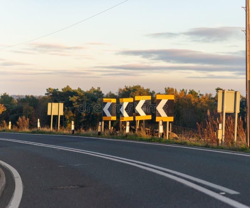 Uma série de sinais adverte motoristas de uma curvatura afiada no Reino Unido fotografia de stock royalty free