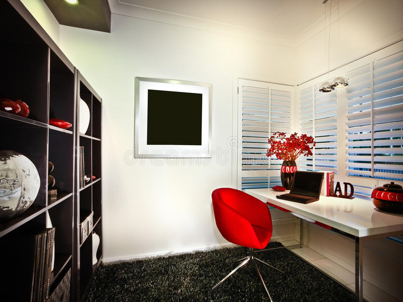 Uma sala de estudo com as bibliotecas da janela e e um portátil colocado sobre fotografia de stock