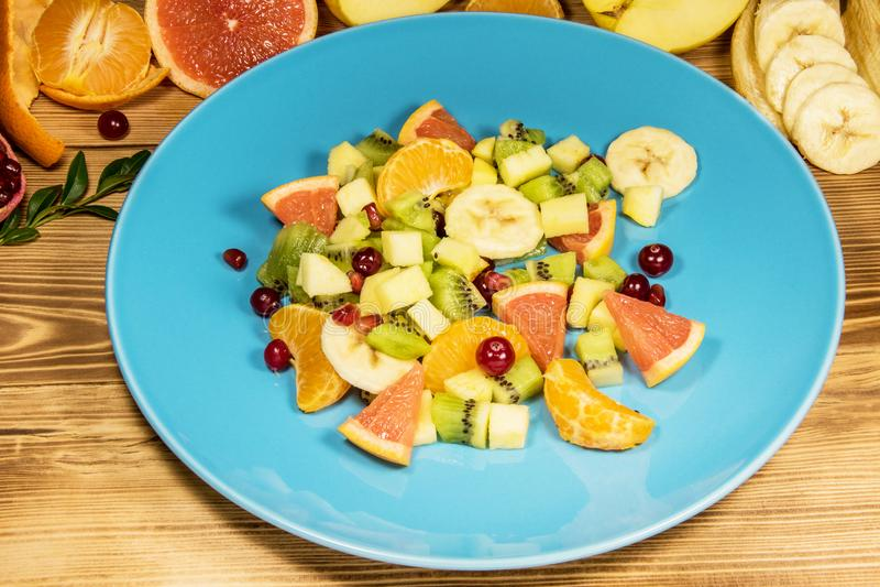 Uma salada dietética fresca do fruto e do citrino é cortada em uma placa azul A placa está em uma tabela de madeira, conceito da  imagem de stock royalty free