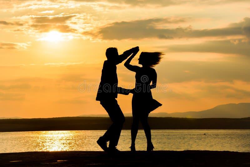 Uma salsa da dança dos pares no por do sol por uma água foto de stock