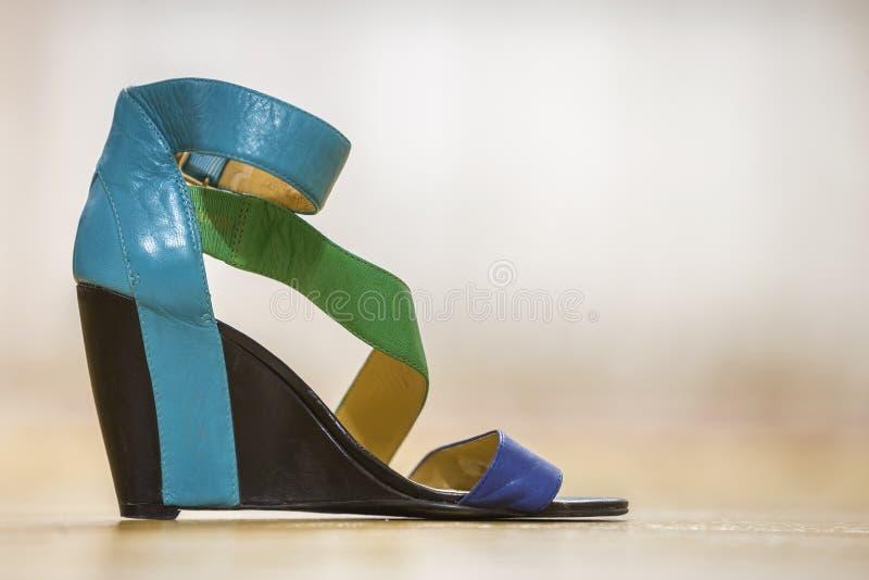 Uma sandália fêmea azul, verde e amarela brilhante colorida da sapata da correia de couro na plataforma preta alta isolada no esp fotos de stock