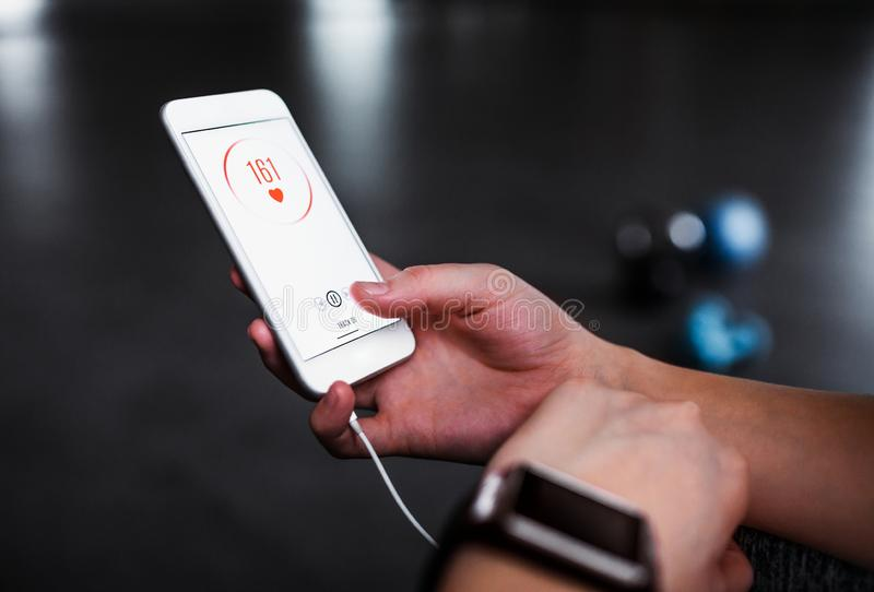 Uma seção mestra da mulher com smartphone em um gym, verificando a frequência cardíaca fotografia de stock royalty free
