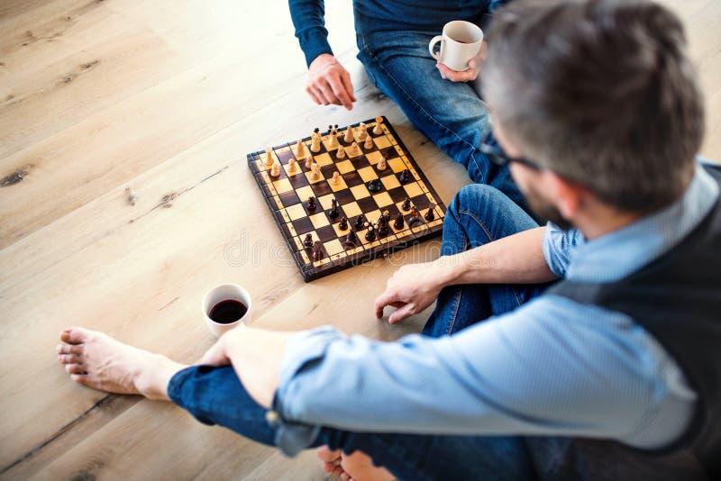 Uma se??o mestra do filho adulto e do pai superior que sentam-se no assoalho dentro, jogando a xadrez fotos de stock royalty free