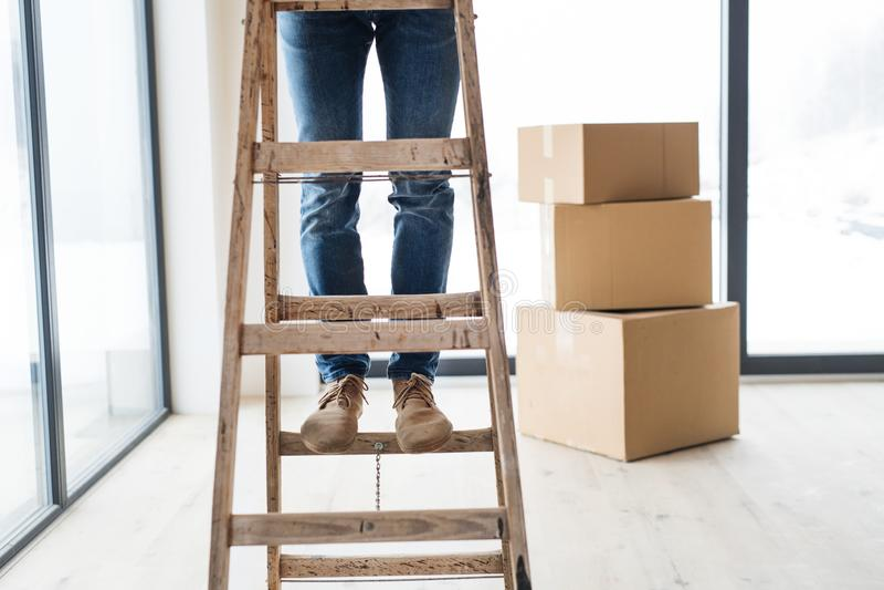 Uma seção mestra do homem com as caixas de cartão que estão em uma escada, casa nova de equipamento fotos de stock