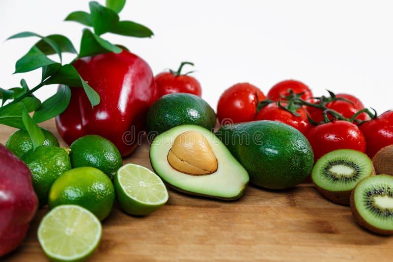 Uma seleção de frutas e legumes suculentas em um fundo de madeira e branco foto de stock