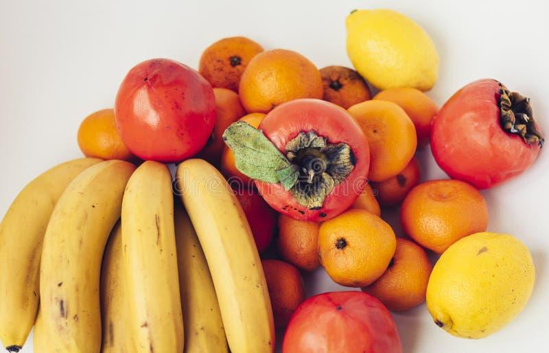 Uma seleção de frutos frescos diferentes arranjados das bananas, dos mandarino, dos caquis e dos limões no fim branco do fundo ac fotografia de stock