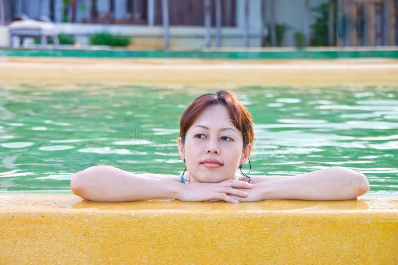 Uma senhora asiática que relaxa na piscina imagem de stock royalty free