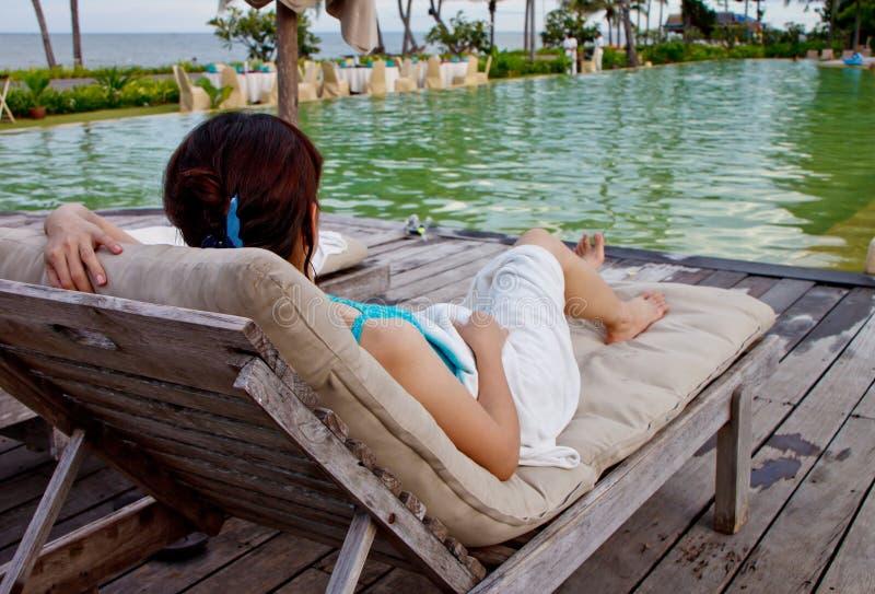 Uma senhora asiática que relaxa na piscina imagem de stock