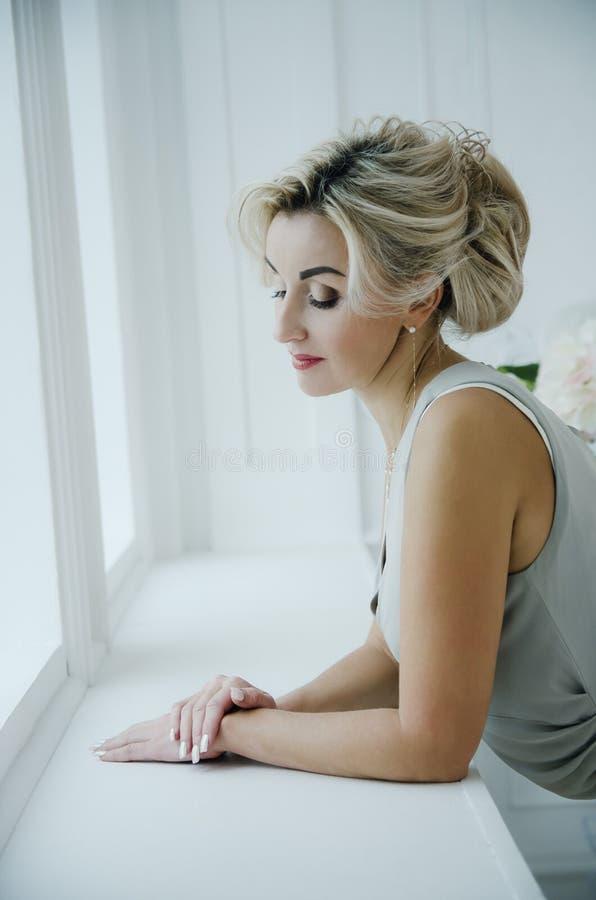 Uma senhora bonita de 40 anos em um vestido de nivelamento longo olha para fora a janela imagem de stock royalty free