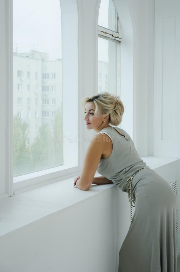 Uma senhora bonita de 40 anos em um vestido de nivelamento longo olha para fora a janela imagens de stock royalty free