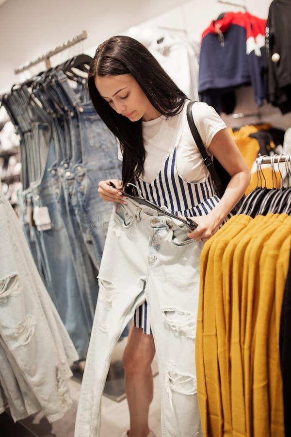 Uma senhora bonita jovem com cabelo longo, roupa ocasional vestindo, está escolhendo calças de brim novas em uma loja famosa fotografia de stock
