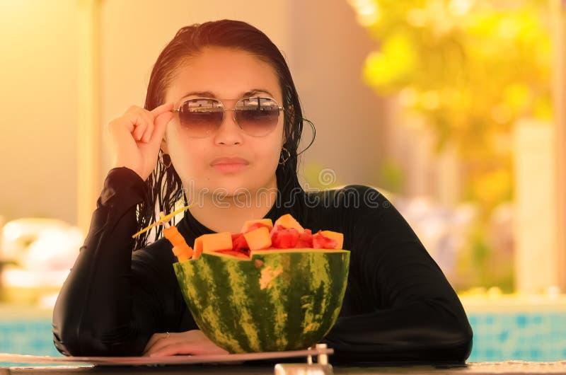 Uma senhora bonita na frente dos frutos sortidos foto de stock royalty free