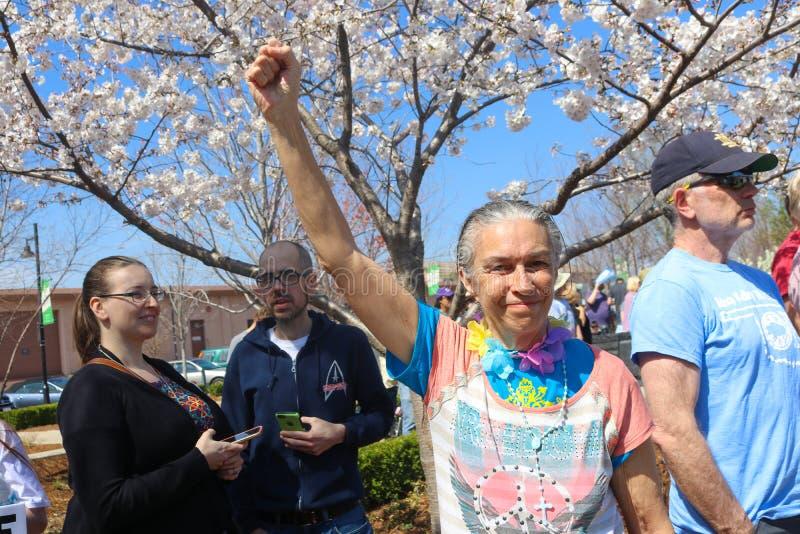 Uma senhora de cabelo cinzenta mais idosa com o t-shirt colorido do sinal de paz e sorriso determinado e seu punho aumentou no ar fotografia de stock royalty free