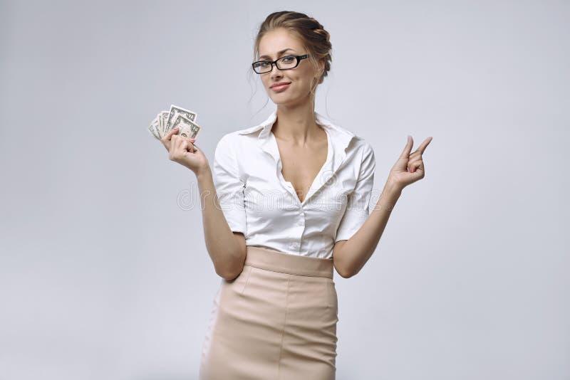 Uma senhora do negócio guarda pouco dinheiro em seu assistente e sua mão esquerda mostra que há dinheiro muito pequeno imagens de stock royalty free