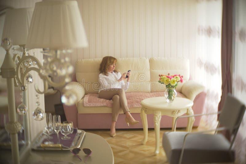 Uma senhora elegante vestiu-se em uma blusa branca e em uma calças bege Uma jovem mulher usa um telefone celular dentro com imagem de stock royalty free