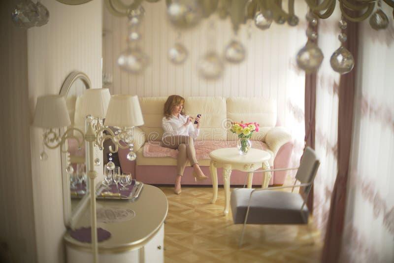 Uma senhora elegante vestiu-se em uma blusa branca e em uma calças bege Uma jovem mulher usa um telefone celular dentro com fotografia de stock royalty free