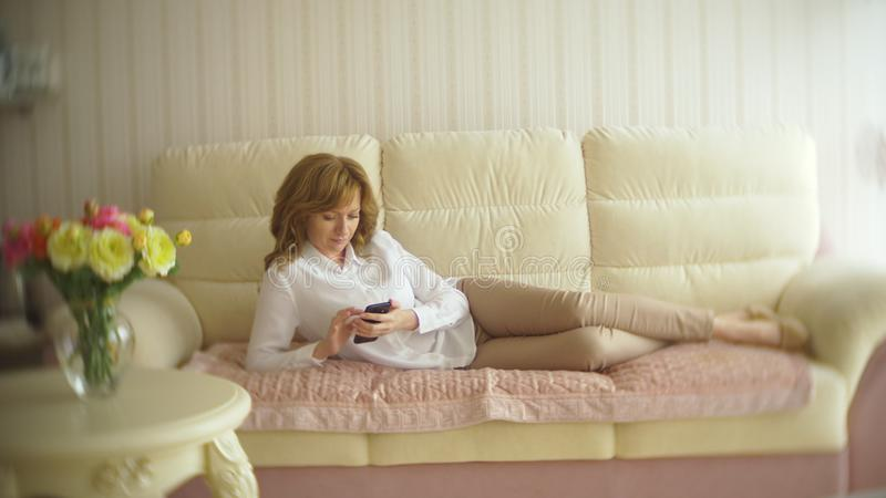 Uma senhora elegante vestiu-se em uma blusa branca e em uma calças bege Uma jovem mulher usa um telefone celular dentro com fotos de stock