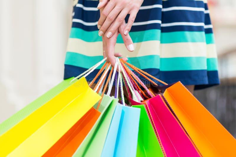 Uma senhora em uma saia está guardando muitos sacos de compras coloridos imagem de stock