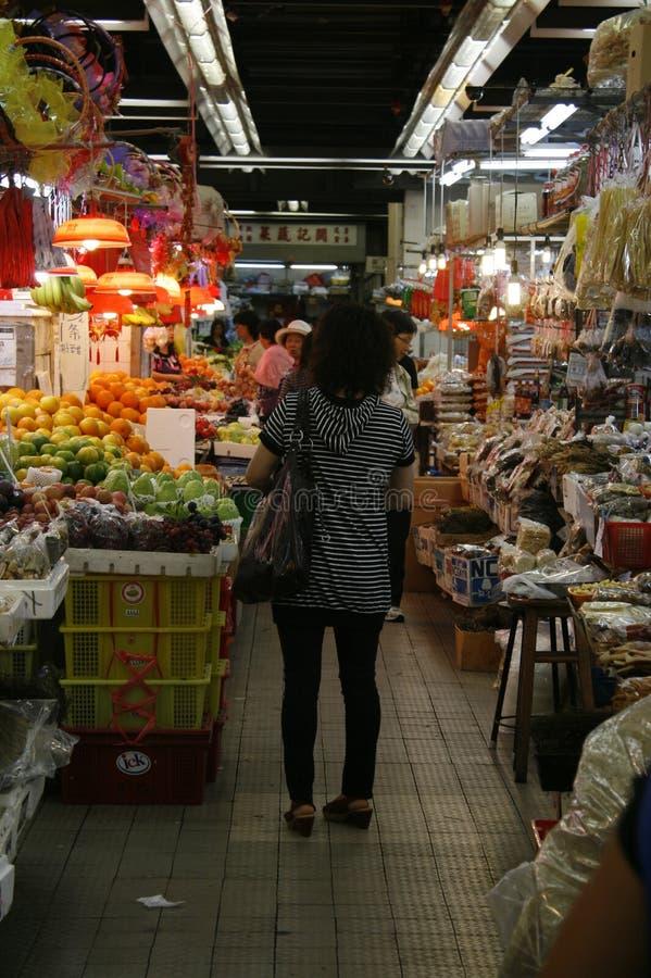 Uma senhora está com ela de volta à câmera em uma ilha do mercado de Sheung Shui fotografia de stock royalty free