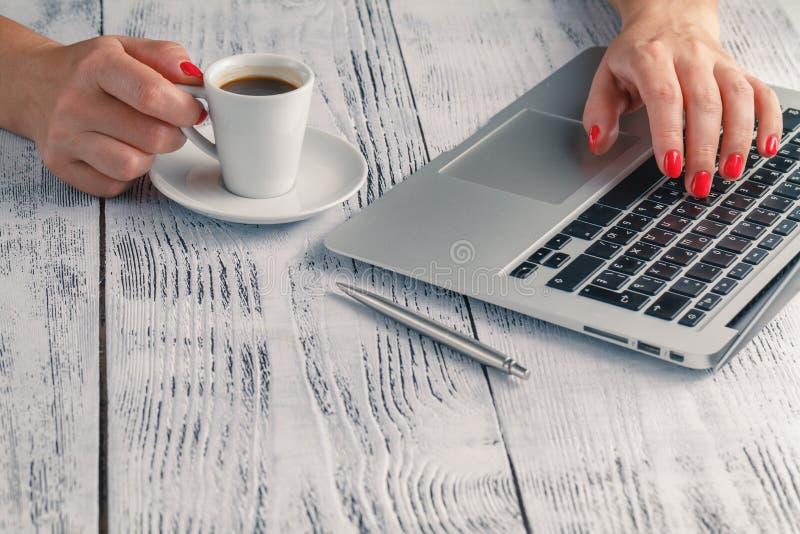 Uma senhora está guardando o café em sua mão na mesa do PC fotografia de stock royalty free