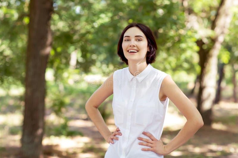 Uma senhora feliz em um fundo ensolarado do parque Uma mulher segura com mãos nos quadris Um trabalhador profissional fora Esfera imagens de stock royalty free