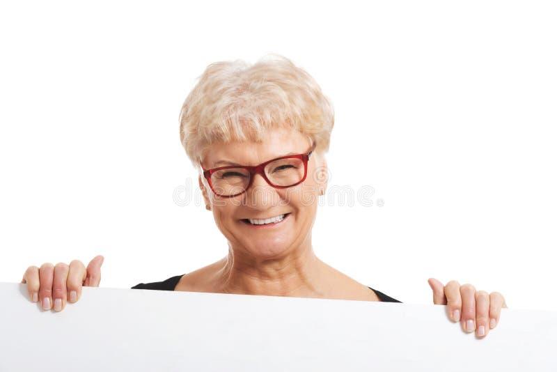 Uma senhora feliz idosa que guarda o espaço da cópia. fotos de stock