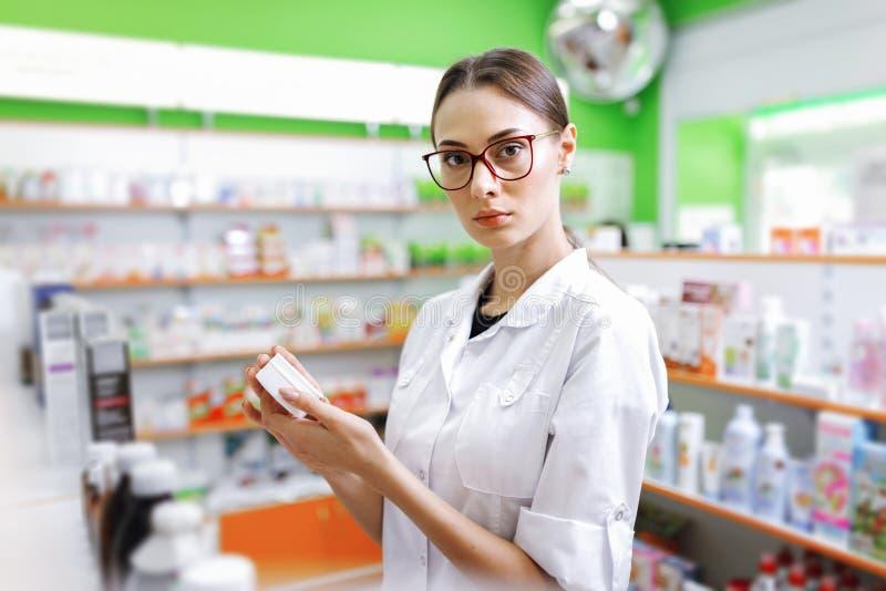 Uma senhora moreno fina nova com os vidros, vestidos em um revestimento branco, olha a câmera e guarda um frasco pequeno no imagens de stock