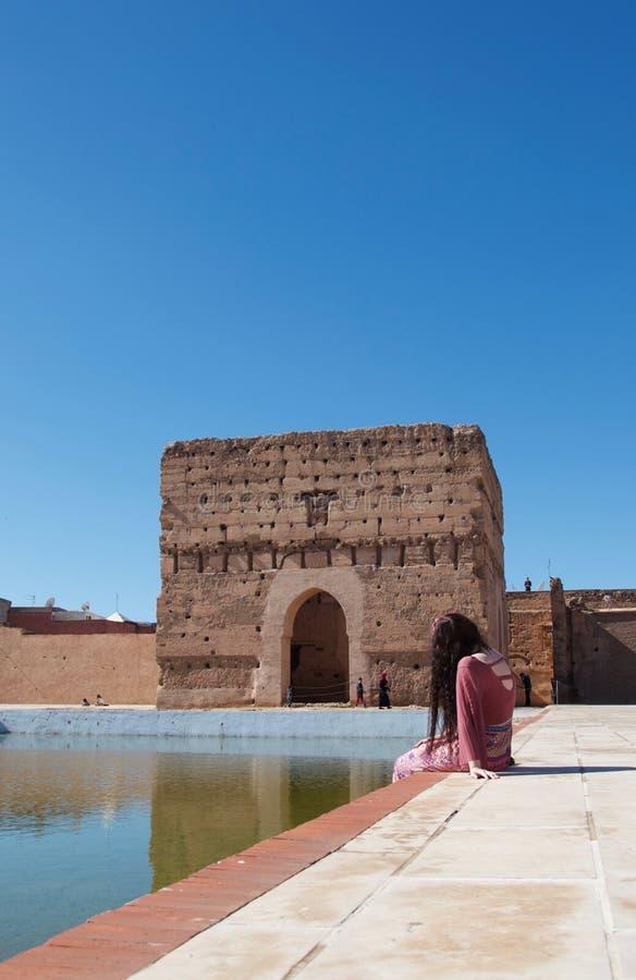 Uma senhora que senta-se por uma lagoa em um palácio marroquino fotografia de stock royalty free