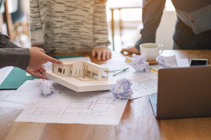 Uma sensação do arquiteto forçou após o trabalho no modelo da arquitetura junto com o papel de desenho da loja na tabela no escri fotografia de stock