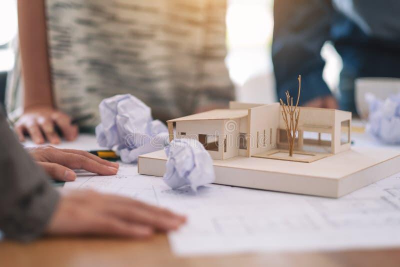 Uma sensação do arquiteto forçou após o trabalho no modelo da arquitetura junto com o papel de desenho da loja na tabela no escri imagem de stock royalty free