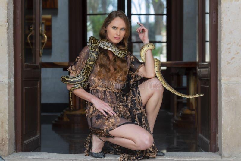 Uma serpente moreno latino-americano bonita do Constrictor de boa de Poses With A do modelo em torno de seu corpo fotos de stock royalty free