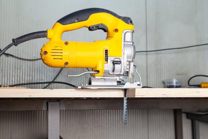 Uma serra de vaivém elétrica amarela está de modo operacional em um material de construção de madeira visto em uma bancada em uma imagem de stock royalty free