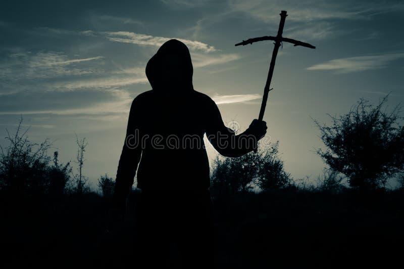 Uma silhueta assustador de uma posição encapuçado do homem fora de guardar uma cruz caseiro de madeira no por do sol Com um vinta imagem de stock royalty free