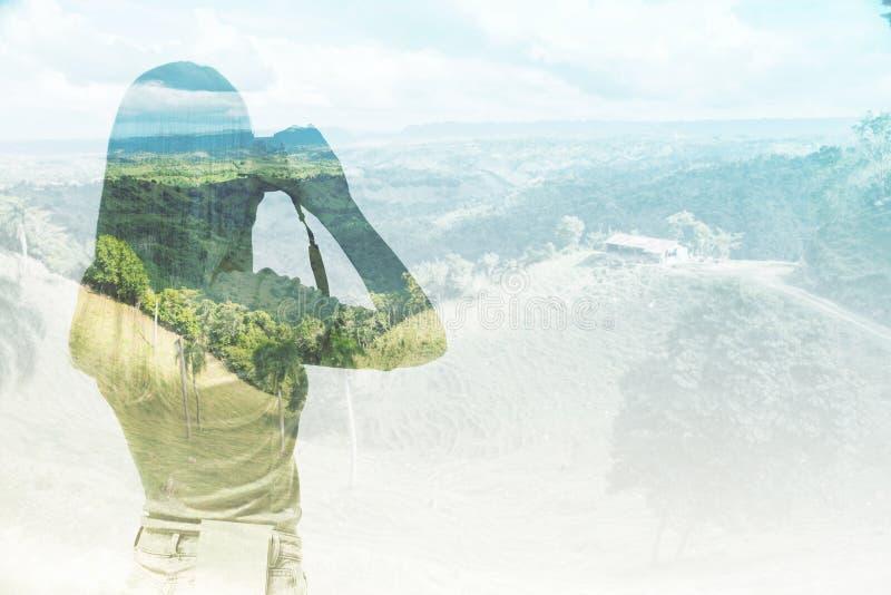 Uma silhueta da jovem senhora que está tomando uma imagem da paisagem imagens de stock royalty free