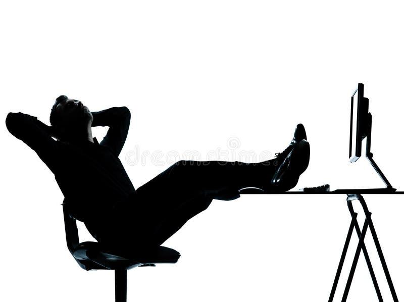 Uma silhueta de relaxamento do computador do homem de negócio imagem de stock royalty free