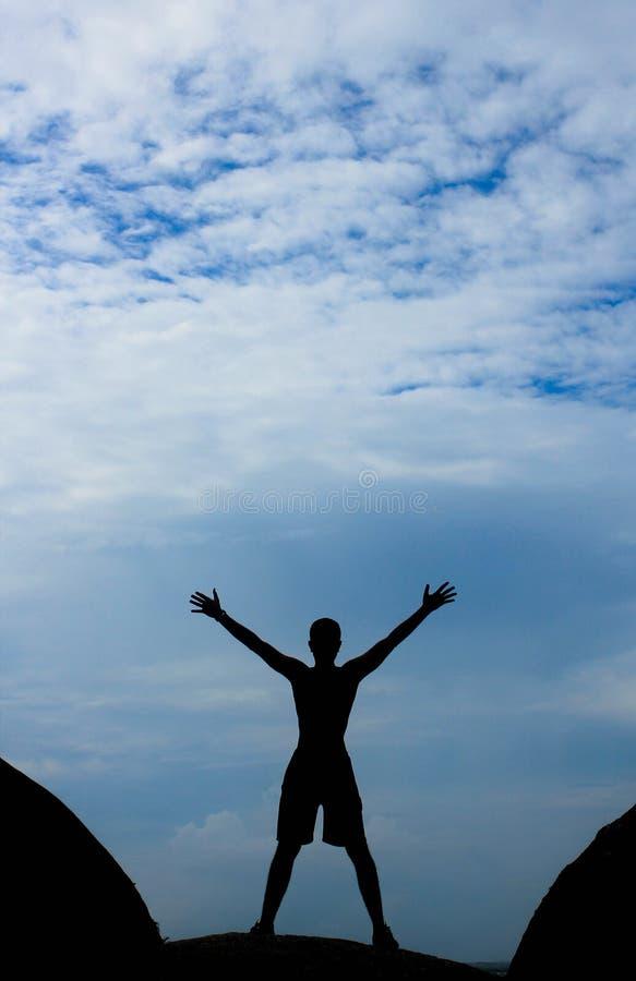 Uma silhueta de um homem com braços abertos imagem de stock