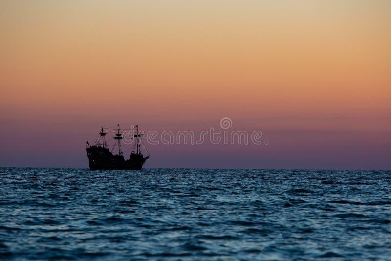 Uma silhueta de um navio de navigação de três mastros como dirige para fora no golfo imagens de stock royalty free