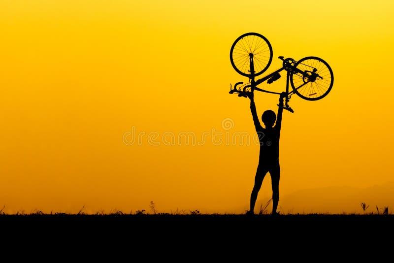 Uma silhueta do homem que levanta acima da bicicleta fotos de stock royalty free