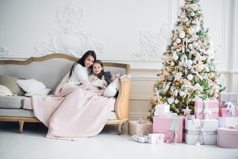 Uma situação de duas meninas felizes, de mãe e de filha em um sofá no Natal decorou a sala imagens de stock royalty free