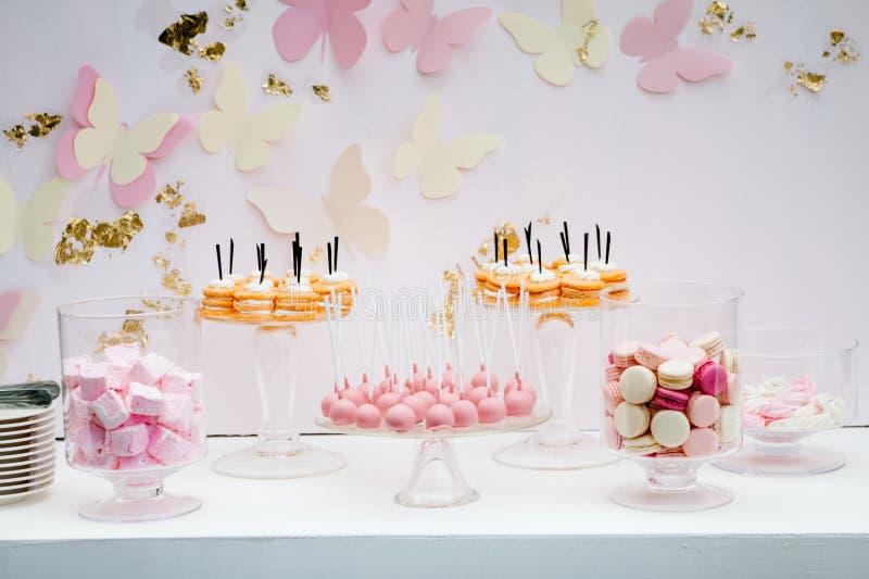 Uma sobremesa doce bonita com um kem branco pairoso Bolos da parcela Bolinhos de amêndoa carmesins brancos cor-de-rosa Marshmallo imagem de stock