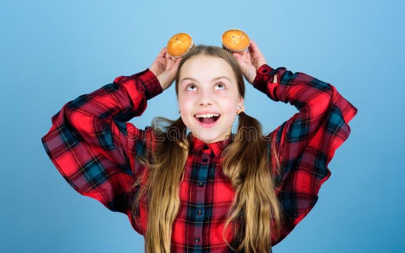Uma sobremesa serviu Sorriso feliz da crian?a pequena com a sobremesa do queque na cabe?a A menina feliz aprecia comer o curso da imagens de stock