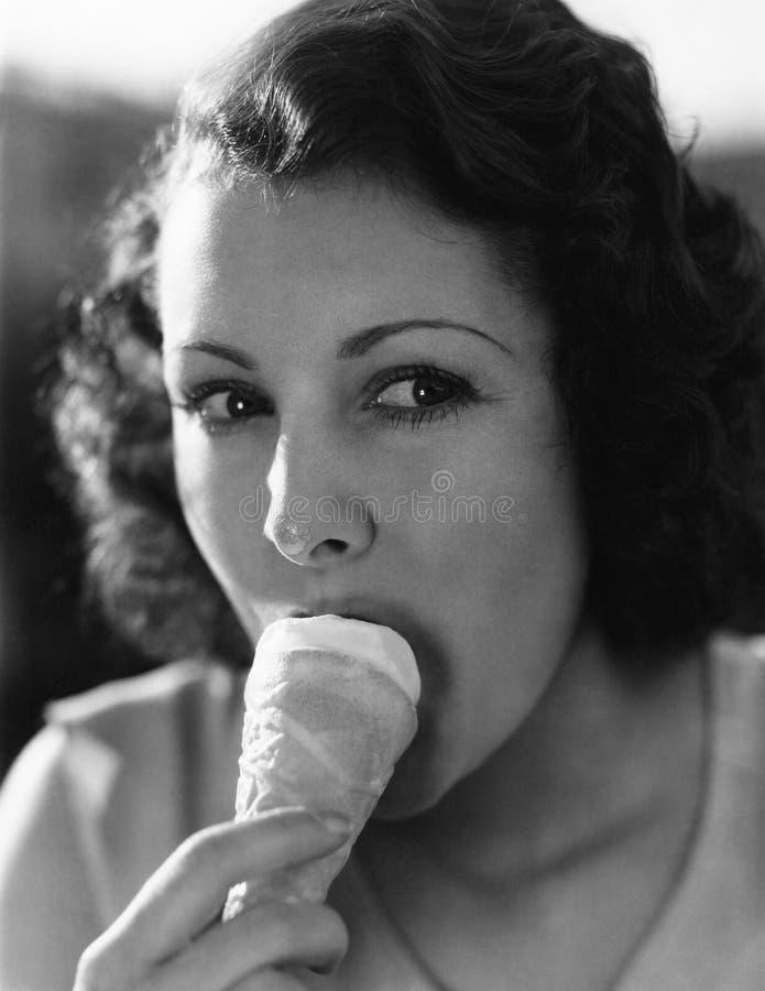 Uma solha pequena no nariz fará o you como uma jovem mulher come o gelado de um cone (todas as pessoas descritas não são umas viv fotos de stock