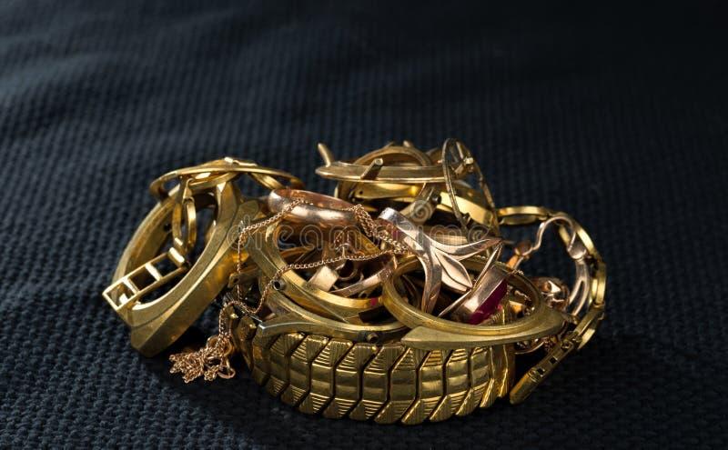 Uma sucata do ouro Joia velha e quebrada, relógios do ouro e folheado a ouro em um escuro - azul imagens de stock