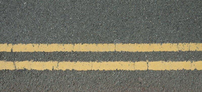 Uma superfície de estrada lascando-se de pedra com linhas amarelas dobro imagem de stock royalty free