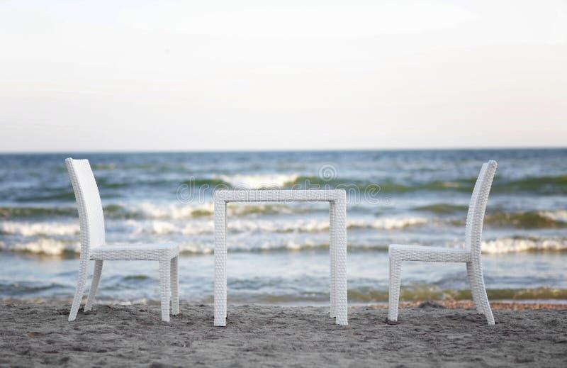 Uma tabela branca e duas cadeiras confortáveis em um fundo bonito do mar A atmosfera romântica na praia Mobília na natureza imagens de stock royalty free