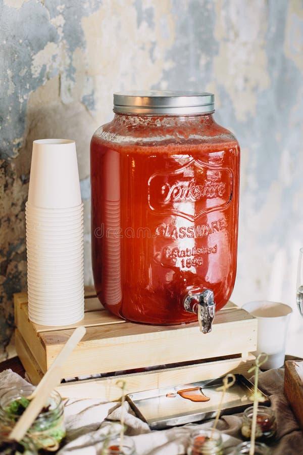 Uma tabela de bufete decorada bonita em um partido com o distribuidor de vidro com limonada, os copos de papel e os petiscos nos  foto de stock