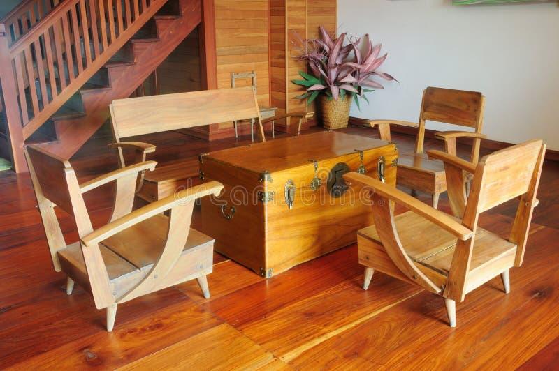 Uma tabela de console da teca e uma poltrona de madeira no assoalho de madeira imagens de stock
