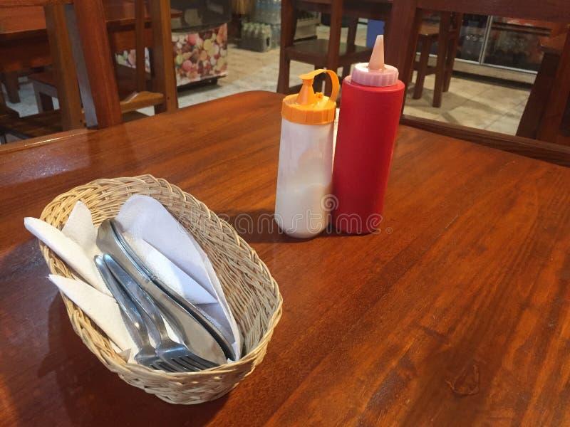 Uma tabela de jantar em um restaurante com ketchup, Mayo e cuttelry fotografia de stock royalty free