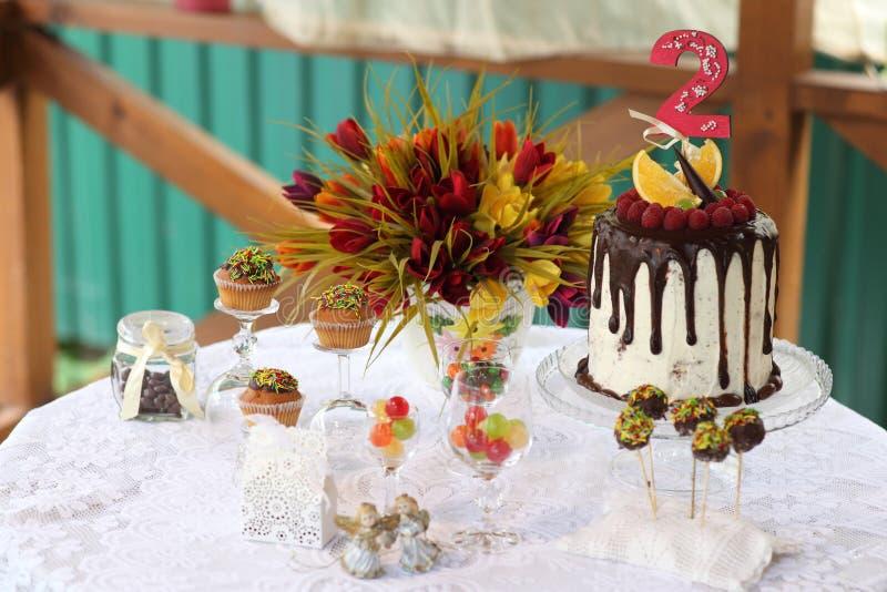 Uma tabela festiva decorada com o bolo de aniversário com flores e doces foto de stock royalty free